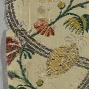 Fragment of a cream-colored silk with diagonally intersecting lattice of silver and cream-colored threads. Over this lattice are yellow pieces of fruit and delicate curving floral vines in green, red and blue-gray.