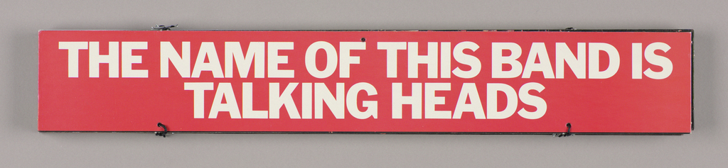 Eight slats, attached vertically by thin black cord about three inches in from the left and right edges, comprise this promotional mobile for a record album titled The Name of This Band is Talking Heads. Just above the bottom edge of the eighth slat on both recto and verso, one line of type in small white capitals contains the names of the record producers and object photographers.  Recto: When the object is folded, only slat number 1 is visible: The Name Of This Band Is/Talking Heads, imprinted in gold white sans serif style capitals on a red ground. When unfolded, all eight slats are visible. Number 6 is identical to number 1. The remaining slats feature color photographic reproductions of four of the band's musicians performing on their instuments (2-5), along with two audience members seated in the lower right hand corner (7-8). White tied-back curtains and a framed print hung on the white wall point to the performance taking place in a domestic venue.