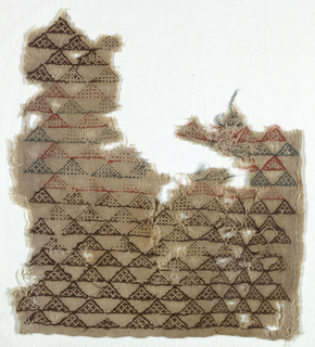 Section of coarse undyed linen cloth with small-scale allover pattern of triangles set side-by-side in diagonal rows, some filled with crosses, some filled with counted darning stitch. In dark brown, blue-green, and rust-red wools. One plain selvage.