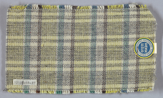 Warp in stripes of yellow, white, green, and brown cotton. Wool weft in stripes of grey and white. Overall plaid effect.