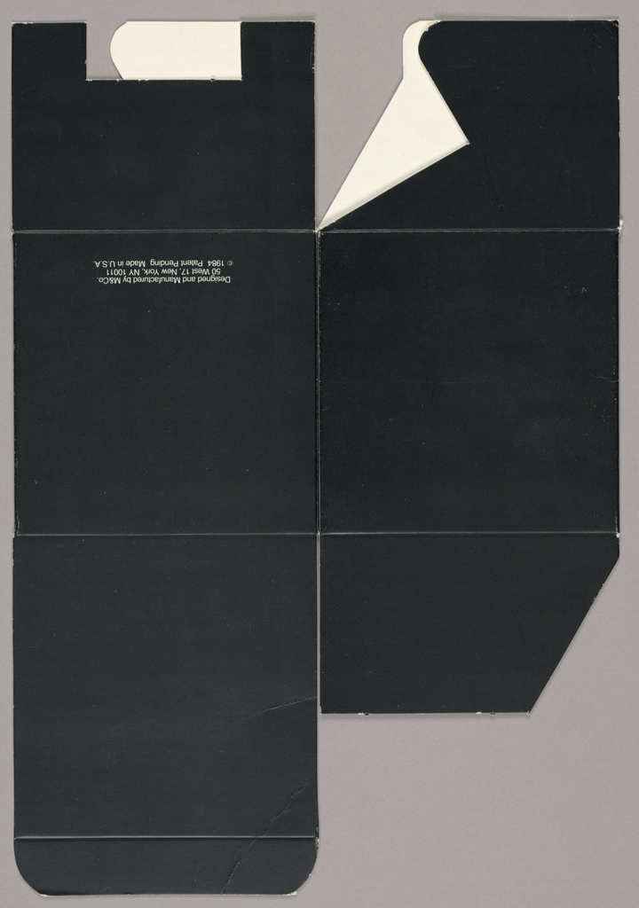 Recto: The black coated cardboard box, designed to hold an M&Co gift paperweight (model unspecified), is imprinted on the front panel on the right, just off center, with unjustified left and right margins, in white italicized type: An object/ designed to hold/ down loose/ papers by its weight. On the back panel, just above the bottom edge, centered, are three lines of sans serif white type: Designed and Manufactured by M&Co/ 50 West 17, New York, NY 10011/ [copyright symbol] 1984 Patent Pending Made in U.S.A. Verso: blank white cardboard.
