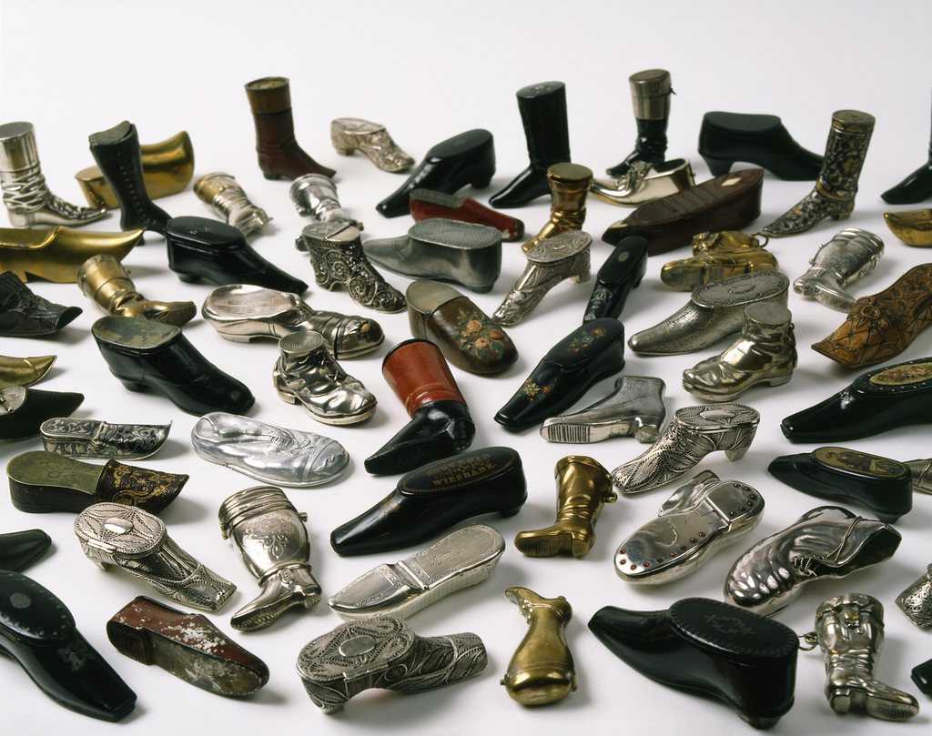"""In the shape of a slightly elongated, black, square-toe shoe, with low heel, gold printed decoration of buckle/bow at instep, top (lid) inscribed """"Souvenir de Wiesbade"""" surrounded by decorative oval border. Lid hinged on upper part of long side. Striker on sole of shoe."""