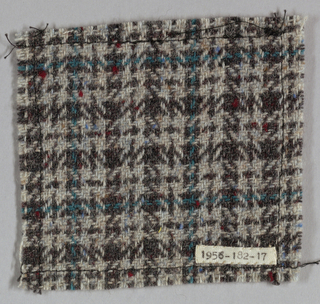 Very fine blue-green windowpane check overlaying a houndstooth in brown on an oatmeal ground with red and blue flecks.
