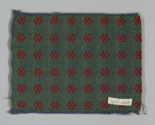Blue cotton warp and green wool weft with extra red weft lancé to create regular pattern of red rosettes on green ground.