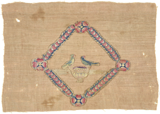 Within a frame of overlapping hearts, two birds on each side of a cup or chalice. Mounted onto another fabric.
