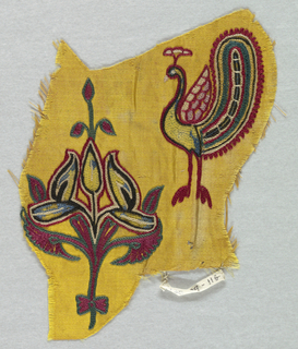 Yellow satin embroidered in chain stitch with a design of a peacock and a floral ornament.