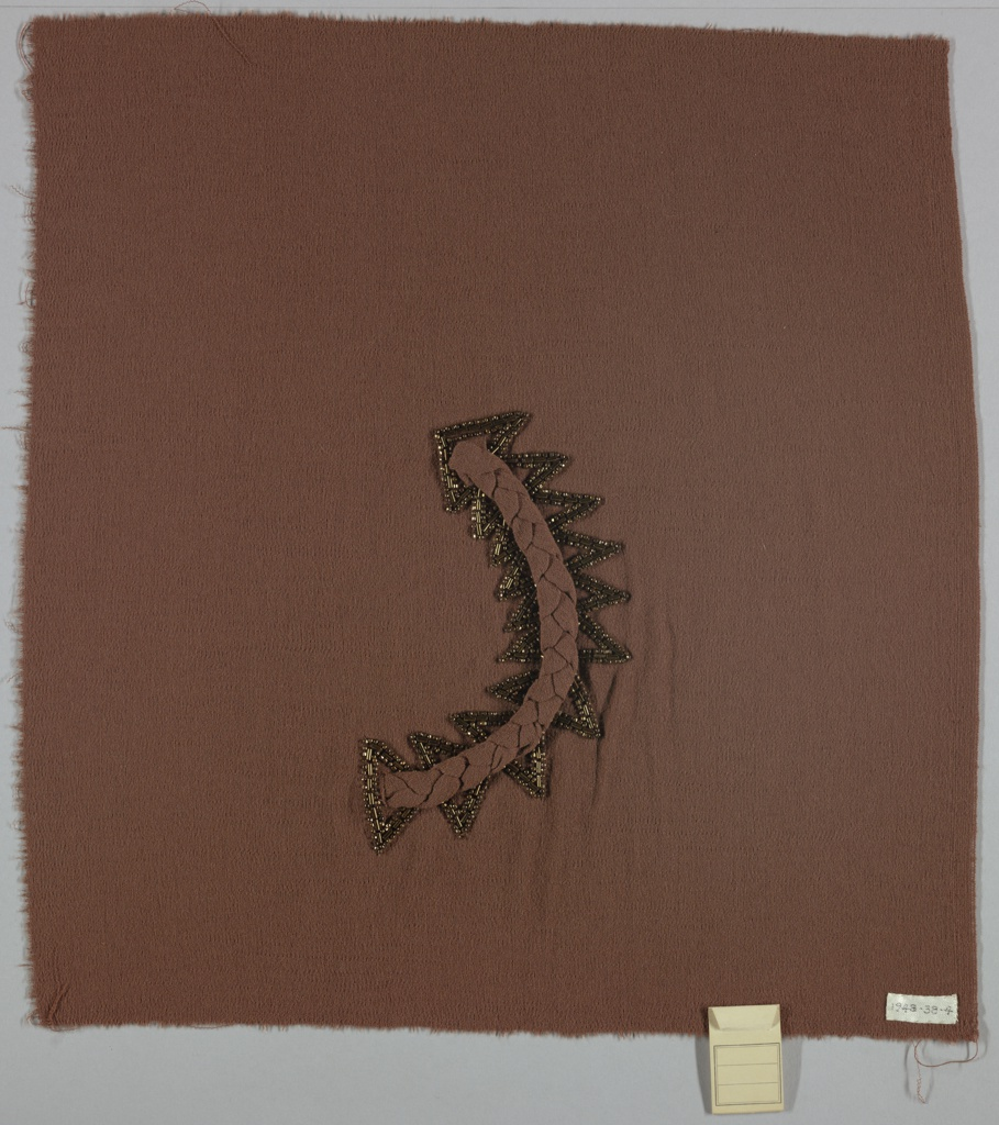 Panel of brown cloth appliquéd with a twisted band of the same cloth in the shape of semi-circle. Brown beads embroidered around the semi-circle in a saw tooth pattern form an arrow shape.