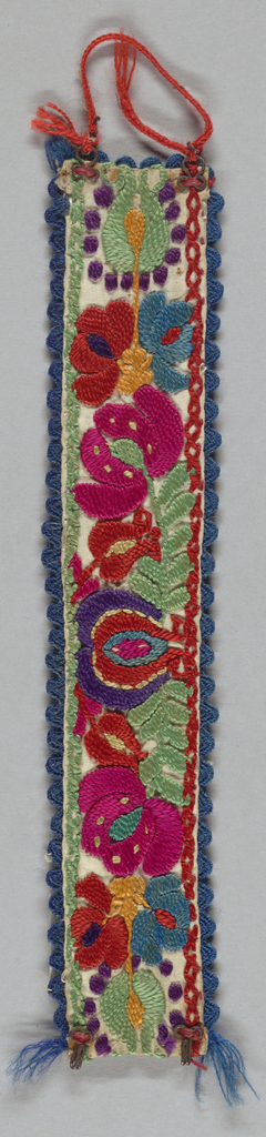 White linen with embroidery of fruit with a flower spray on either side. Edged with rickrack braid. Two steel hooks and eyes with a chain of wool between eyes.