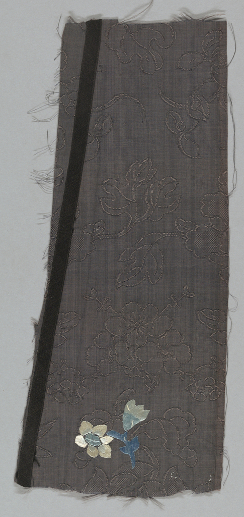 Fragment of silk gauze embroidered with small scale flowers and buds in blue and white on a dark blue ground that is self-patterned with a design of cherry blossoms. Probably a fragment of a summer robe.