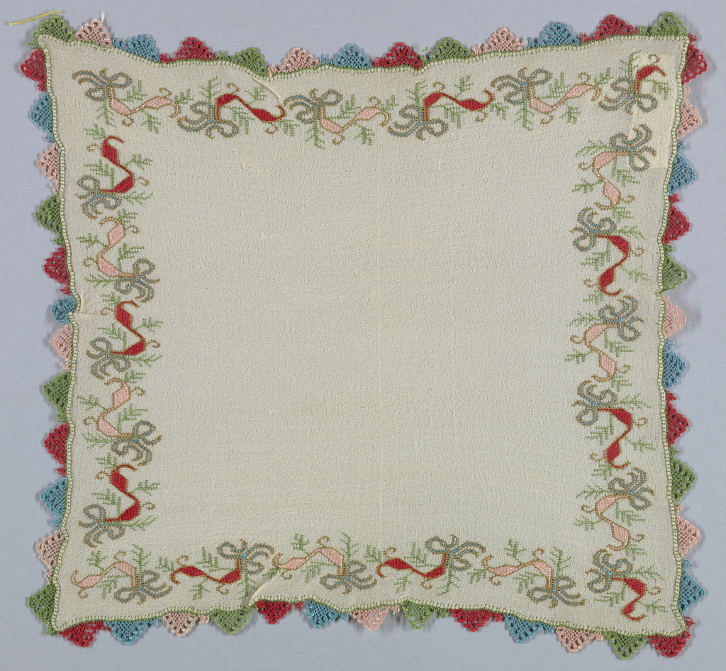 White handkerchief with embroidered border and needle knotted bibila edging in blue, green, red and pink.