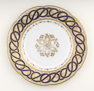 Circular plate, the scalloped rim having tan ground with applied interlaced curving blue bands and gilt floral border; the well with a stylized gilt floral decoration in the center.