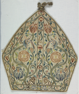 """Front and back from a mitre; white satin, embroidered in polychrome silks and gold thread. Design, which is same front and back, shows, in left and right spaces, and ascending vine with various flowers, rose, etc. ; in blue, shades of rose, white, light green; long tailed bird perched on upper stem is stooping toward a flower, and is embroidered in blue, pink and with black ends to tail and feathers. Center, as smaller ascending vine, with various birds and border (1-1/4"""" wide) of similar vine with birds. Design outlined with gold thread. Stitches mostly satin with some knot stitch. Trimmed at pointed top with gold tassels. Sides of mitre are on stiff linen, interlined with linen, and with remains  of white taffeta lining."""