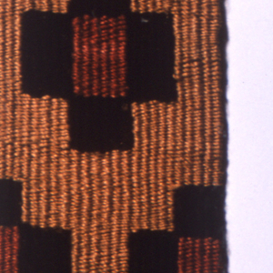 Narrow woven band with repeats of geometrical motifs in red, dark brown and yellow. Blue welts on warps of natural cotton and brown wool twisted together.