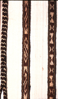 """Long narrow wool band with series of """"S"""" repeats, series of angular scroll repeats, and series of rectangular repeats made up of triangles, in dark green, red, white; framed top and bottom with green, yellow, brown guard stripes.  Warps at each end plaited in two strips which merge into single thicker plait after 1""""; separate again 1"""" from end and terminate in 4"""" fringe; chevron striped in plaited area from different warp colors."""