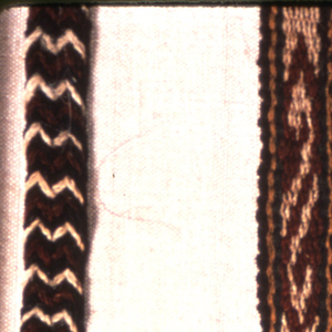 "Long narrow wool band with series of ""S"" repeats, series of angular scroll repeats, and series of rectangular repeats made up of triangles, in dark green, red, white; framed top and bottom with green, yellow, brown guard stripes.  Warps at each end plaited in two strips which merge into single thicker plait after 1""; separate again 1"" from end and terminate in 4"" fringe; chevron striped in plaited area from different warp colors."