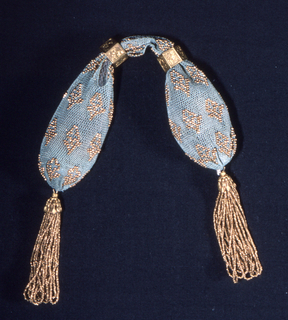 Netted silk of cerulean blue color, ornamented with gold beads in diamond pattern. Side opening controlled by two etched hexagonal gold rings; gold bead tassels at each end.