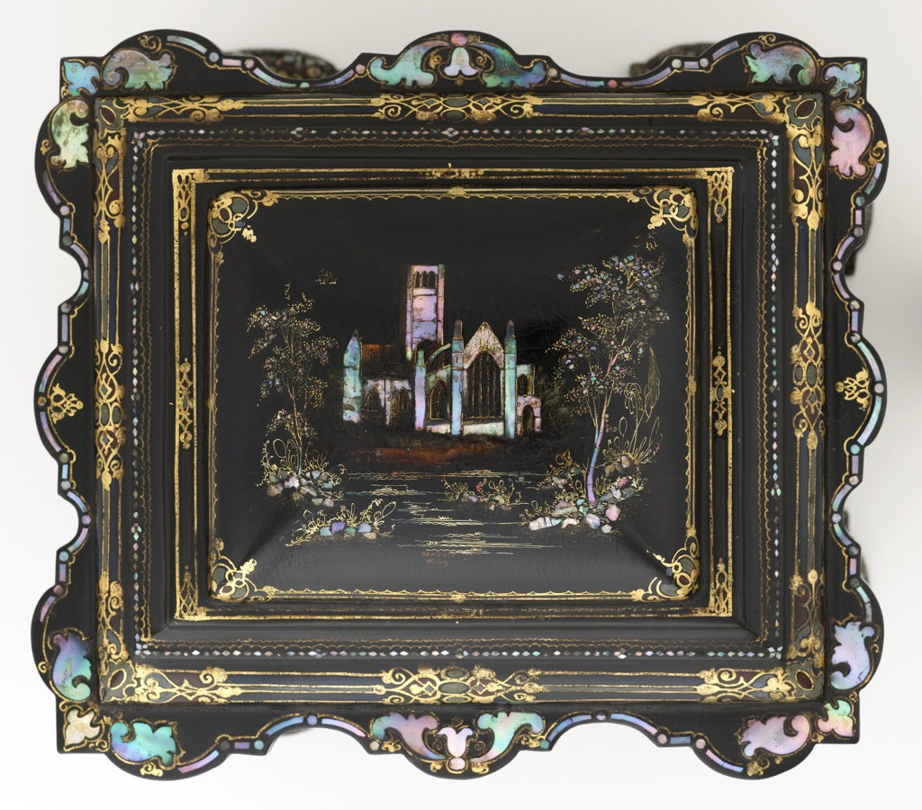 "Elaborately contoured square box with stepped, slightly domed, hinged lid with scalloped edges; stepped, scalloped base with four broad feet; the black lacquer ground with overall floral and foliate decoration of mother-of-pearl inlay, gilding and touches of paint; lid with scene of large church in landscape, ""Melrose Abbey"" in small letters painted under scene; lid opens over compartmented top section; double doors in front open to reveal four drawers, the bottom one designed like a lap desk with hinged flap; drawer and compartment linings of silk, velvet, paper; ivory and mother-of-pearl tape measure container and emery container; small metal key."