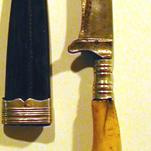 Set consisting of: knife (a) with blade having straight top edge and cutting edge tapered to a point, mounted on curved bone handle with baluster ferrule and metal end. Tapered stitched leather sheath (b) with metal tip guard and reeded metal end collar to hold knife and two-pronged fork (c) with short neck and tapered pin. Sheath's tip guard fitted with screw pocket to accept fork pin and become fork's handle.