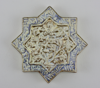 Eight-pointed star tile set in modern silver mounting with pierced gallery. Tile has blue border containing calligraphy surrounding floral design on brownish ground.