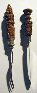 """Fork has four, slightly curved tines, rounded shoulders. Flat flaring neck, octagonal metal socket with twisted wire at edges. Carved wooden handle with four figures; Faith, Hope, Charity and Justice with their attributes, surmounted by scrolls, shell with bird and figure of cherub riding a lion. Around bottom of handle: """"IK.LEEF.OP.HOOP"""" (I am living on hope.) Engraved on socket: KID"""