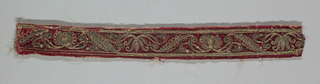 Narrow red band embroidered with stylized floral forms.