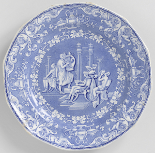 Plate with blue transfer print showing classical figures seated on klismos chairs. Scrollwork border with pottery and grape vines.