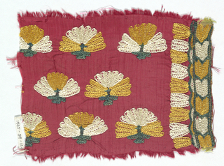 Red ground fabric with embroidery in yellow, green and white in floral pattern.