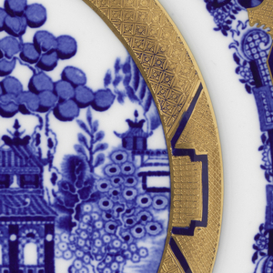 Round plate with blue willow pattern and gold with diaper pattern.