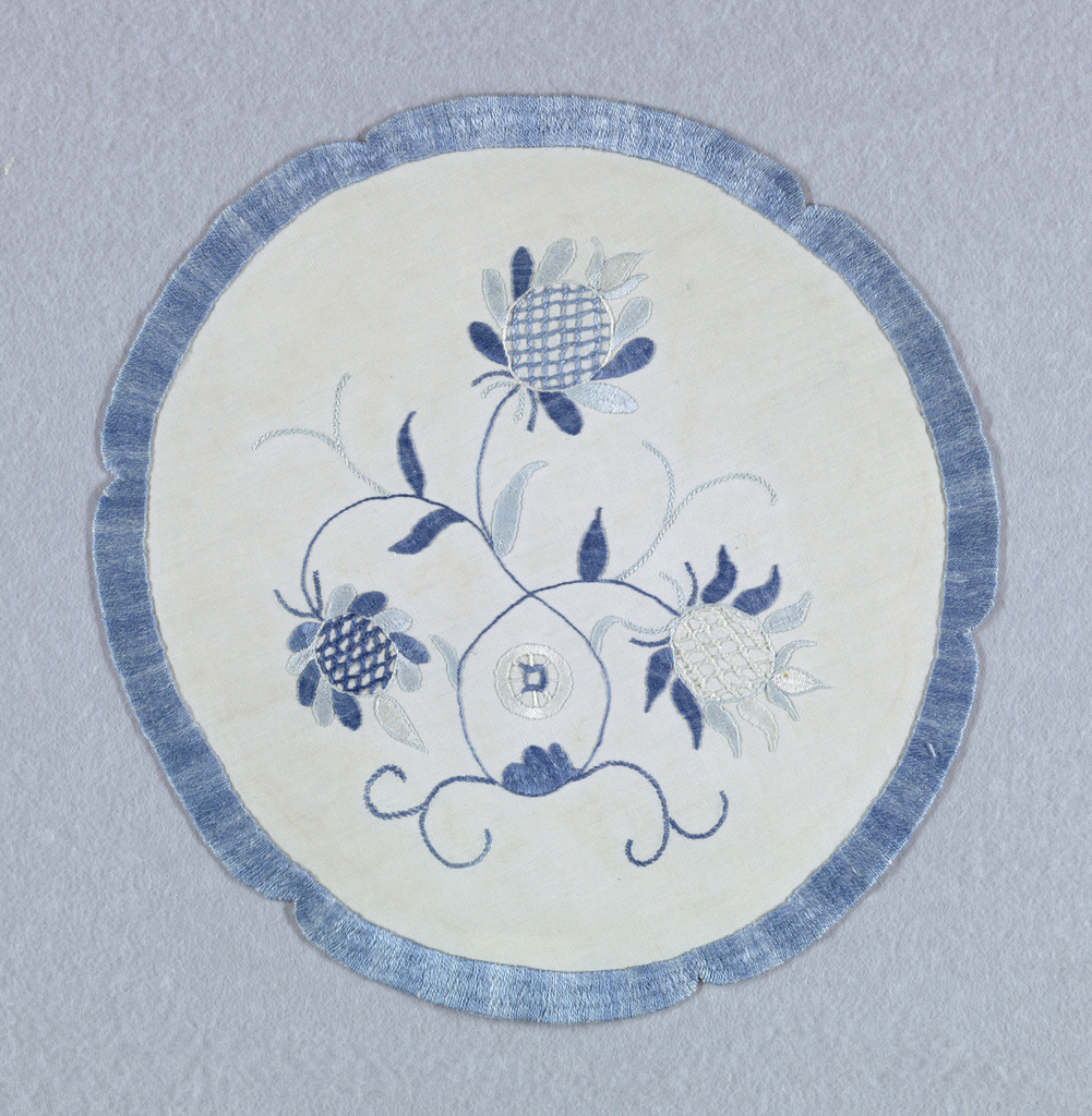"""Plant forms with three exotic blossoms within a notched circle in two shades of blue on a white background. The initial """"D"""" appears within a wheel-like shape in the center."""