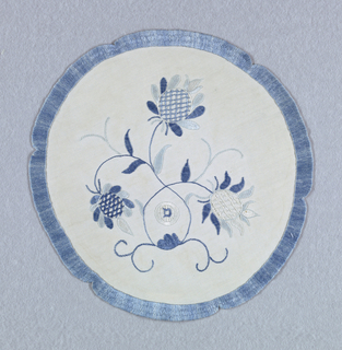 "Plant forms with three exotic blossoms within a notched circle in two shades of blue on a white background. The initial ""D"" appears within a wheel-like shape in the center."