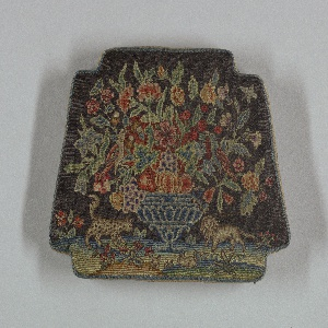 Small chair seat showing an urn of flowers with birds, leopard, lion and rabbits.