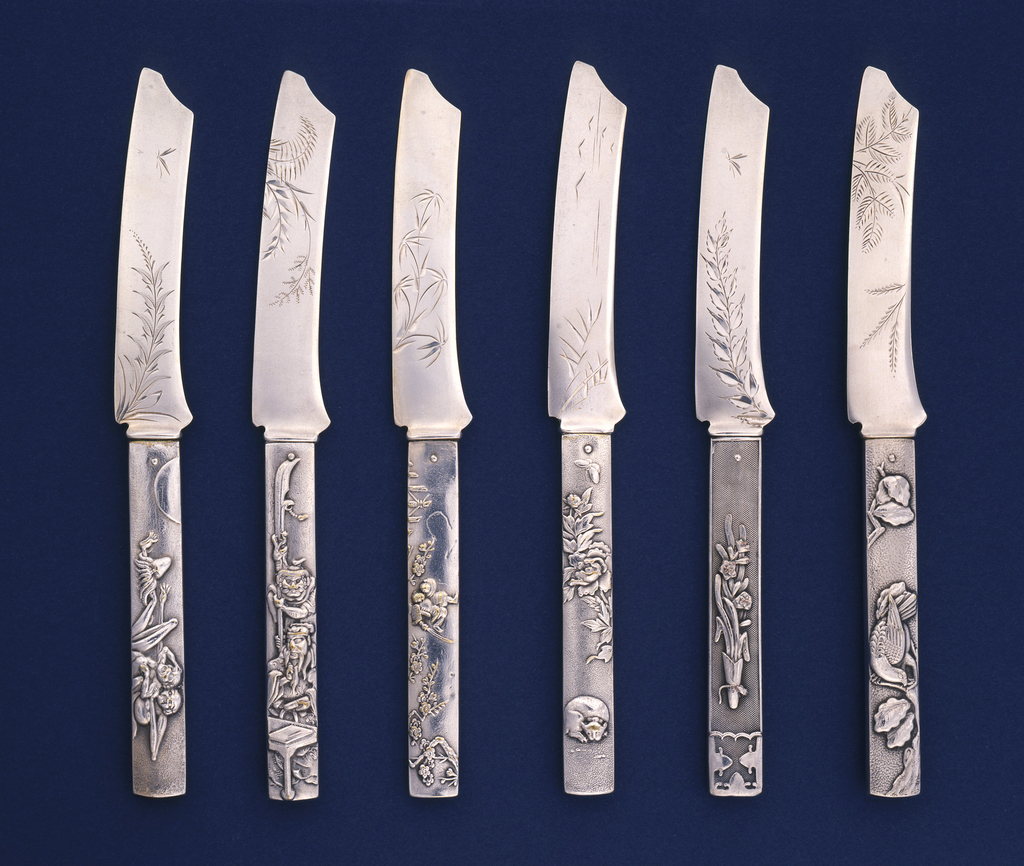 Set of six knives in the form of Japanese swords; handles decorated with Japanesque scenes and characters. Flat, curved blades engraved with stylized foliate decoration.