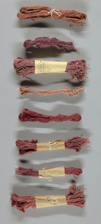 Eight skeins of yarn in various shades of pink. Yarn purchased from a Scottish supplier and dyed by members of the Society.