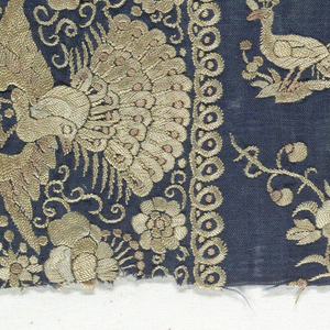 Dark blue silk ground with all-over close embroidery in silks which were originally polychrome, but are now tan. Design on body of piece of profile peacocks alternating with flowering branches. Border of blossoms alternating with peacocks with spread feathers.