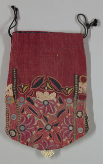 Red linen drawstring bag with a blue silk lining and white tassel at the bottom. Embroidered in the center with a design of stylized flowers and leaves. Narrow borders on the sides enclose circular disks with embroidered borders. Mirrored glass accents.