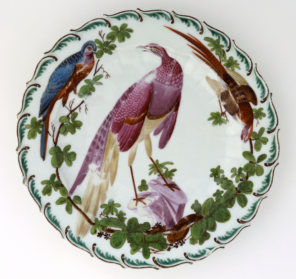 A porcelain and enameled plate with three birds perched on green branches.