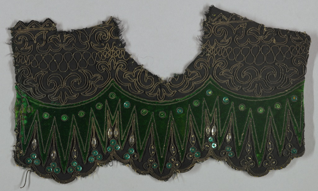 Fragment of black, weft-ribbed silk cut at the bottom into three wide shallow scallops, in turn scalloped, with applied section of bottle green velvet; double row of couched gold cord outlining velvet and encircling applied faceted green glass sequins.