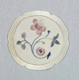 "Stem with two blossoms in muted colors within a notched circle. The initial ""D"" appears in the center of a wheel-like shape."