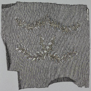 Black net embroidered in a leaf motif comprised of silver leather appliqué for leaves, silver thread and rhinestones for stems.