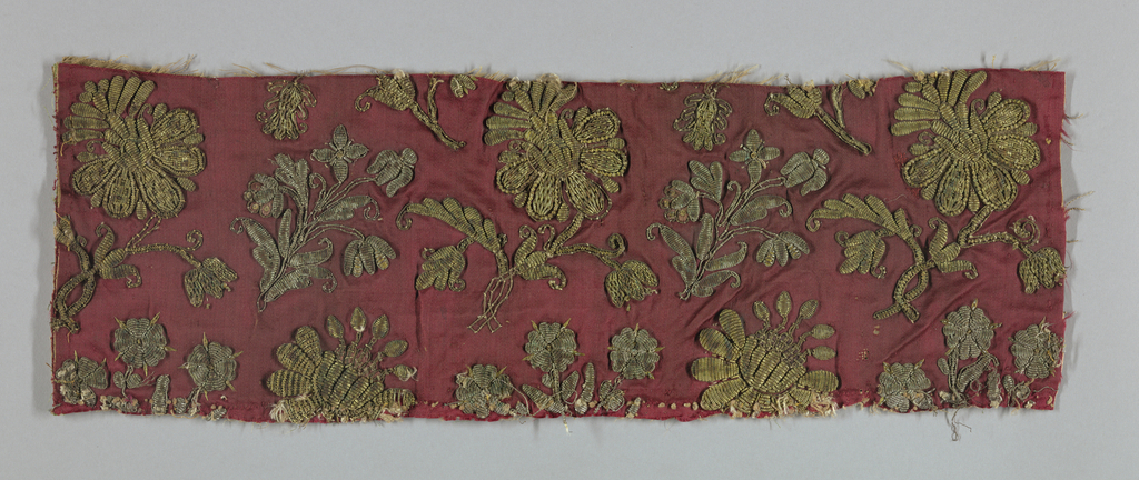 Fragment of an all-over pattern which would have been rows of various flowering plants in alternate alignment in metal-wrapped yarns – gold and silver on a red silk satin. Many areas padded and raised.
