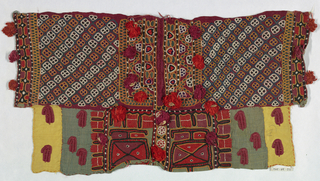 Fragments of green, yellow and red silk pieced together and densely embroidered in a stylized design of geometric and floral motifs. Small tassels with seeds are attached to the sides.