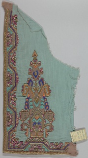 Dress front of pale blue with an embroidered border and central design made of brown appliqué, multi-colored seed beads and gold cord with geometric and floral patterning. Stylized tree shape with floral elements is in the lower center of the dress front.