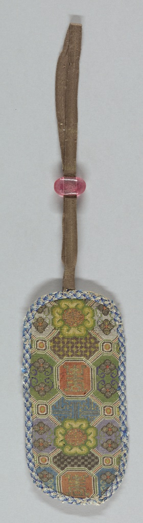 One side of an embroidered spectacle case with geometric and floral designs in polychrome silks. Edged with blue braid and fitted at the top with silk ribbon and a pink bead slide.