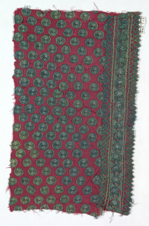 Fragment of a child's tunic with a ground of red silk decorated with green discs and a border at one side of semi-circles and ovals placed in a lattice format with connecting chevrons.
