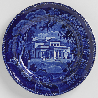 Flat bottom, concave side. Decoration with view of a villa in the Regents Park, London, with trees and figures. Edge with leaf and dot pattern in white reserve. On reverse of edge, name of the decoration on a scroll, surmounted by American eagle.