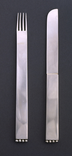 Flat, rectangular in form, handle tapering very slightly towards head; four tines, the head with very, very slight cupping shape; four hollow beads attached at bottom edge of handle.
