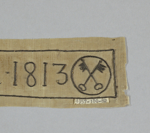 """Strip of white taffeta embroidered in stem stitch, silver wound on thread. """"VIGAR. ECC. ST. P. AN. 1813"""" flanked on one end by a monogram; on the other by crossed keys within a circle."""