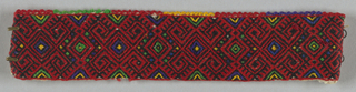 Small rectangle covered by an allover symmetrical design of diamonds and hooks in red and black with touches of purple, green and yellow. One long edge finished with a decorated buttonhole stitch in colors mentioned above.