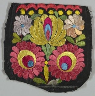 "Cap crown of black cotton embroidered in a brilliantly colored large-scale flower design. The embroidery is worked through and almost identical on the reverse. Ticket attached reads: ""Mezzo Kevech embroidery, Hungary."""