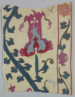 Fragment with silk embroidery showing a stylized flower in shades of red, pink, purple, and light blue with dark blue leafy stems.